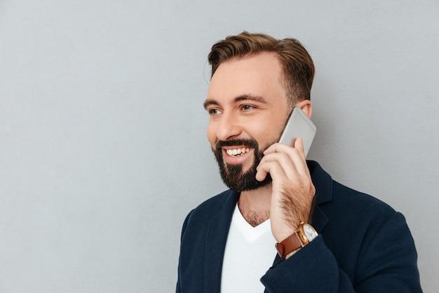Ritratto dell'uomo bello che parla sullo smartphone isolato