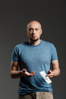 Ritratto dell'uomo bello in camicia grigia che tiene soldi sopra la parete scura