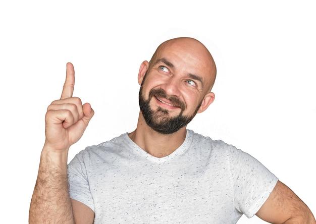 Ritratto dell'uomo calvo bianco con la barba in maglietta bianca che sorride e che mostra pollice su. isolare su uno sfondo bianco