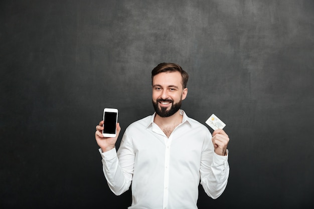Ritratto dell'uomo castana che posa sulla macchina fotografica facendo uso dello smartphone e della carta di credito per acquisto online, isolato sopra grigio scuro