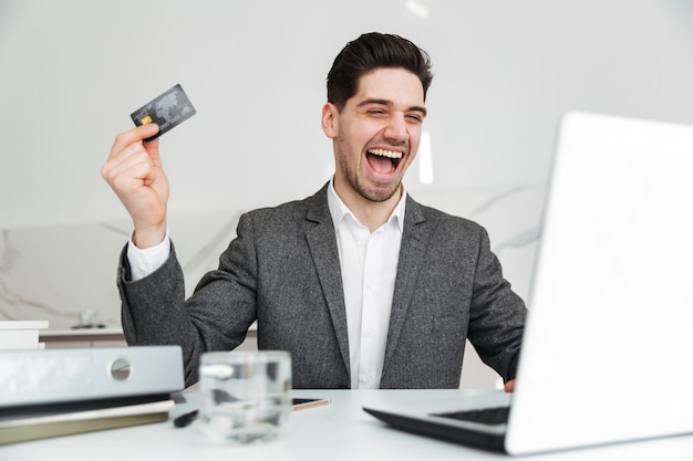 Ritratto dell'uomo castana esultante che si rallegra e che tiene la carta di credito, mentre esaminando taccuino in ufficio