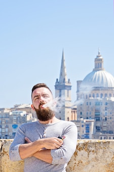 Ritratto dell'uomo caucasico dell'metà di-adulto che fuma sigaretta elettronica,