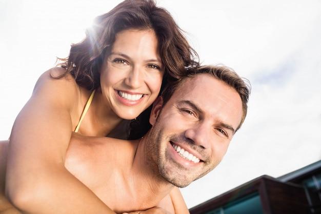 Ritratto dell'uomo che dà sulle spalle alla donna vicino al poolside un giorno soleggiato