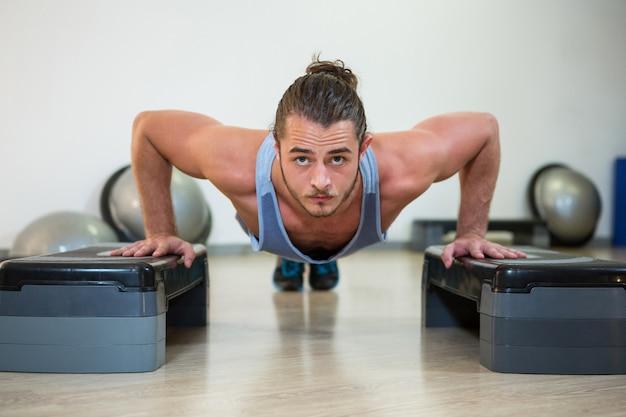 Ritratto dell'uomo che fa esercizio aerobico su passo passo