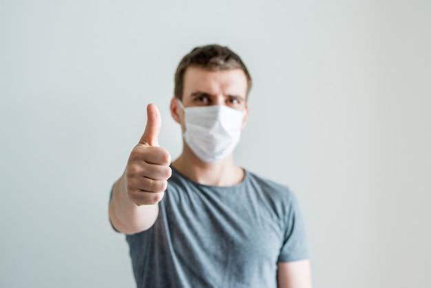 Ritratto dell'uomo che indossa maschera medica bianca ed e pollice su, malattia su fondo leggero. consapevolezza ambientale, concetto di coronavirus e protezione dall'influenza.