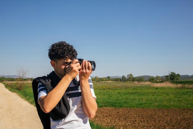 Ritratto dell'uomo che prende fotografando con la macchina fotografica digitale