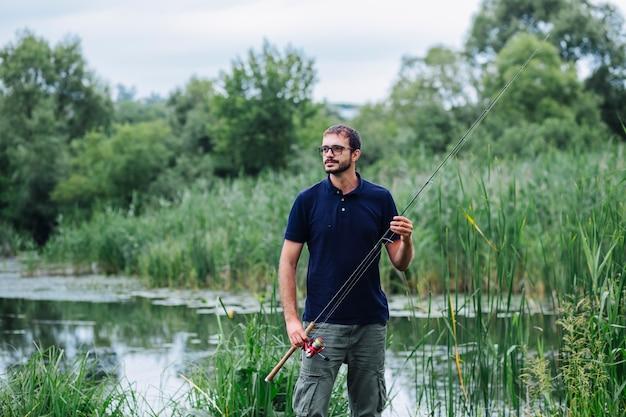 Ritratto dell'uomo che sta vicino alla canna da pesca della tenuta del lago