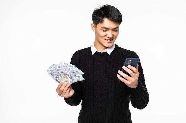 Ritratto dell'uomo cinese emozionante con il telefono in mani che mostrano molte banconote isolate sulla parete bianca