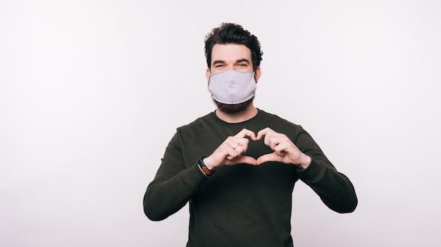 Ritratto dell'uomo con la maschera facciale che fa gesto di amore del cuore
