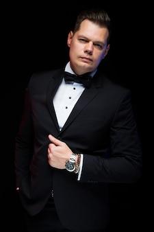 Ritratto dell'uomo d'affari alla moda elegante bello sicuro con il farfallino con la mano sul suo vestito sul nero