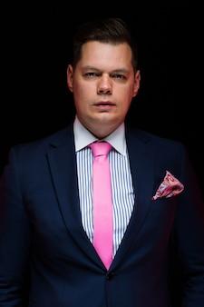 Ritratto dell'uomo d'affari bello sicuro che guarda in camera sul nero