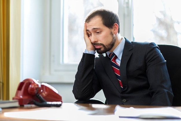 Ritratto dell'uomo d'affari che esamina telefono e che prevede chiamata