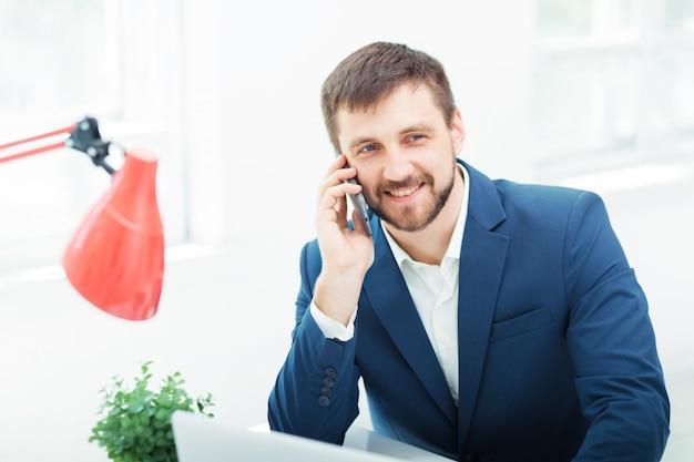 Ritratto dell'uomo d'affari che parla sul telefono in ufficio