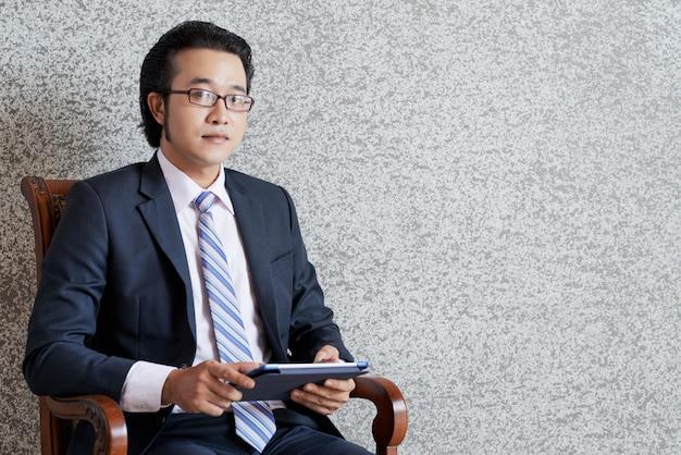 Ritratto dell'uomo d'affari che si siede con la compressa in poltrona e che esamina diritto la macchina fotografica