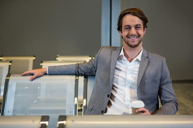 Ritratto dell'uomo d'affari che si siede con la tazza eliminabile nell'area di attesa