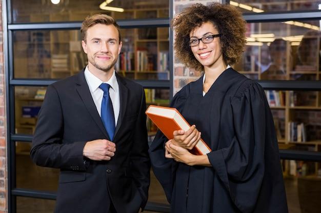 Ritratto dell'uomo d'affari che sta con l'avvocato vicino alla biblioteca in ufficio