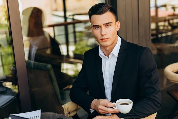 Ritratto dell'uomo d'affari che tiene una tazza di caffè e che esamina la macchina fotografica - immagine