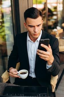 Ritratto dell'uomo d'affari che tiene una tazza di caffè e che esamina lo schermo del telefono cellulare