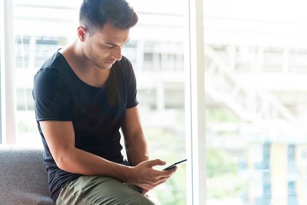 Ritratto dell'uomo d'affari che utilizza cellulare nell'ufficio.