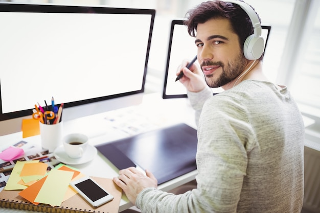Ritratto dell'uomo d'affari che utilizza la tavola dei grafici nell'ufficio