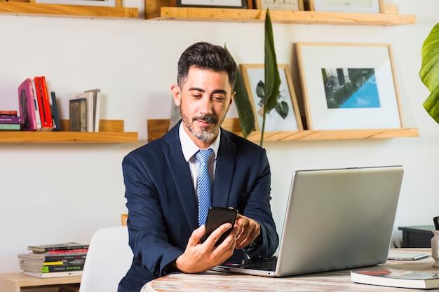 Ritratto dell'uomo d'affari con il computer portatile sulla sua tavola facendo uso del telefono cellulare