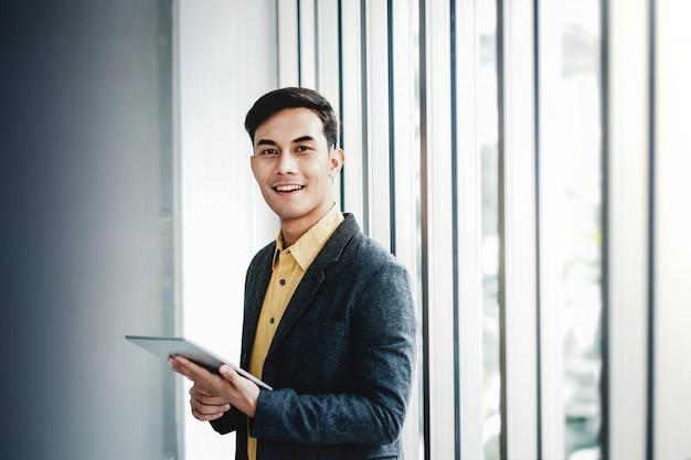 Ritratto dell'uomo d'affari felice che fa una pausa la finestra in ufficio