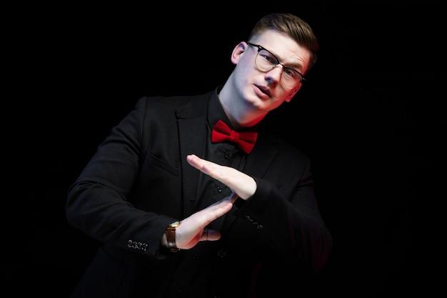 Ritratto dell'uomo d'affari responsabile elegante bello sicuro che mostra gesto di prespegnimento su fondo nero
