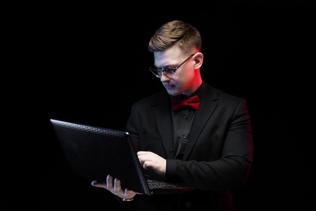 Ritratto dell'uomo d'affari responsabile elegante felice ambizioso bello sicuro che lavora al suo computer portatile