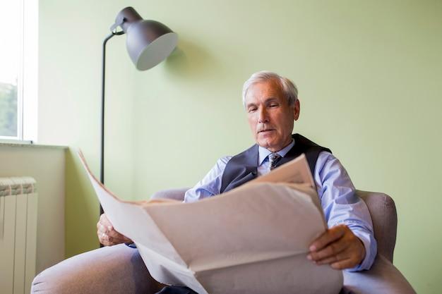 Ritratto dell'uomo d'affari senior che si siede sul giornale della lettura della poltrona