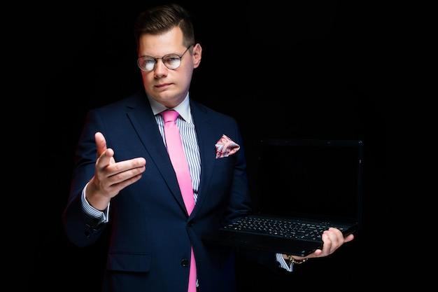 Ritratto dell'uomo d'affari serio bello sicuro che mostra sul computer portatile che fa gesto di mano isolato sul nero