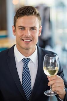 Ritratto dell'uomo d'affari sorridente che tiene un vetro di birra