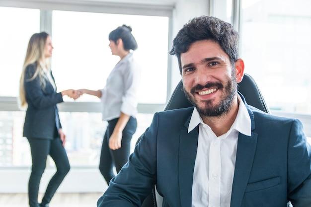 Ritratto dell'uomo d'affari sorridente davanti alle donne che agitano le mani