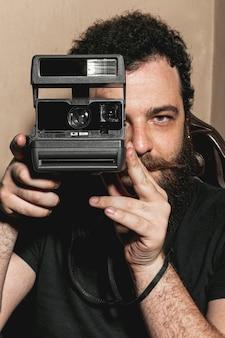 Ritratto dell'uomo dei pantaloni a vita bassa che usando macchina fotografica d'annata