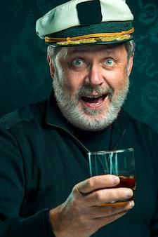 Ritratto dell'uomo del marinaio anziano come capitano in cognac bevente del cappello e del maglione nero sullo studio nero
