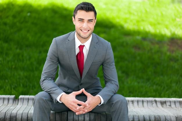 Ritratto dell'uomo di affari che si siede su una panchina all'aperto