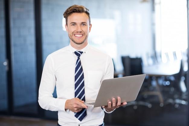 Ritratto dell'uomo di affari che sta con un computer portatile nell'auditorium anteriore in ufficio
