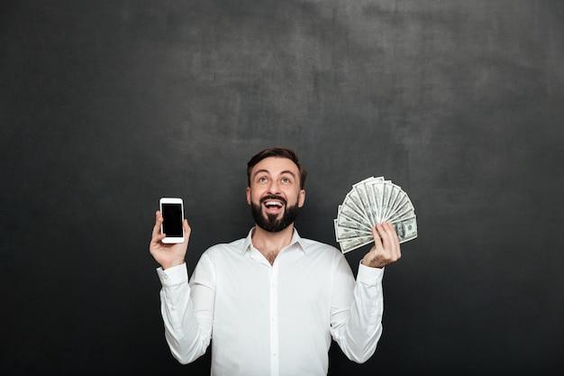 Ritratto dell'uomo estatico che esprime i guadagni online con la tenuta dei lotti della valuta e dello smartphone del dollaro dei soldi, isolato sopra grigio scuro