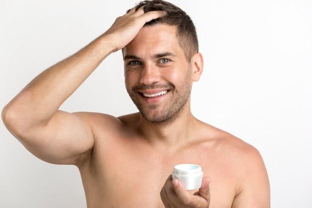 Ritratto dell'uomo felice che applica la cera dei capelli che sta contro il fondo bianco