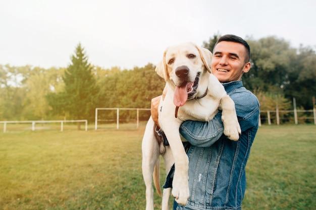 Ritratto dell'uomo felice che tiene il suo cane labrador dell'amico al tramonto in parco
