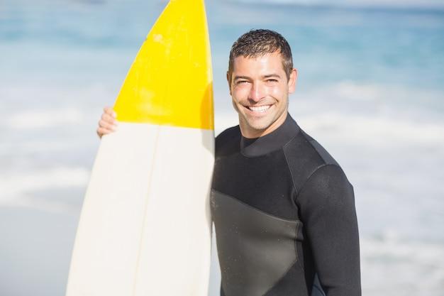 Ritratto dell'uomo felice che tiene una tavola da surf sulla spiaggia