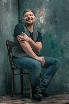 Ritratto dell'uomo felice sorridente che si siede sulla sedia di legno sullo studio grigio