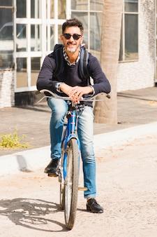 Ritratto dell'uomo moderno che indossa occhiali da sole neri che si siedono sulla bicicletta