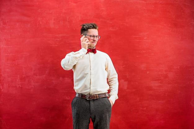 Ritratto dell'uomo perplesso che parla dal telefono su rosso