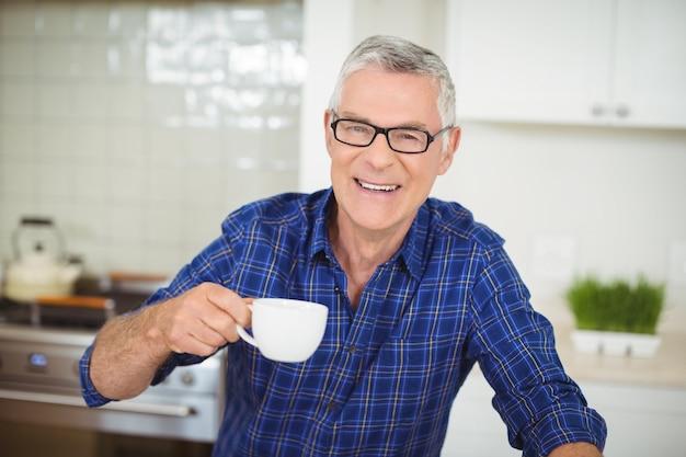 Ritratto dell'uomo senior che mangia tazza di tè nero