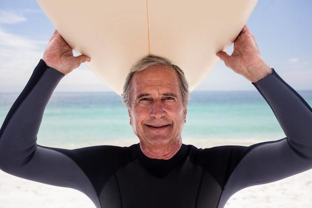 Ritratto dell'uomo senior che tiene una tavola da surf sopra la sua testa