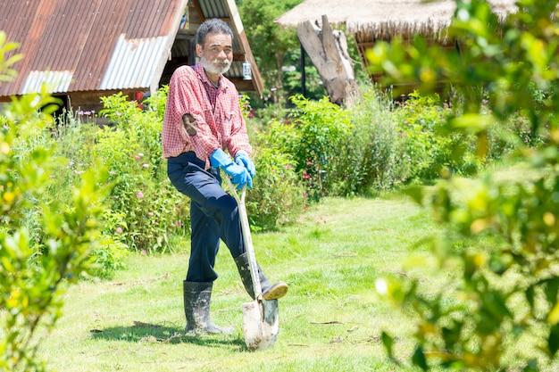 Ritratto dell'uomo senior con gli strumenti di giardinaggio che funzionano nel giardino.