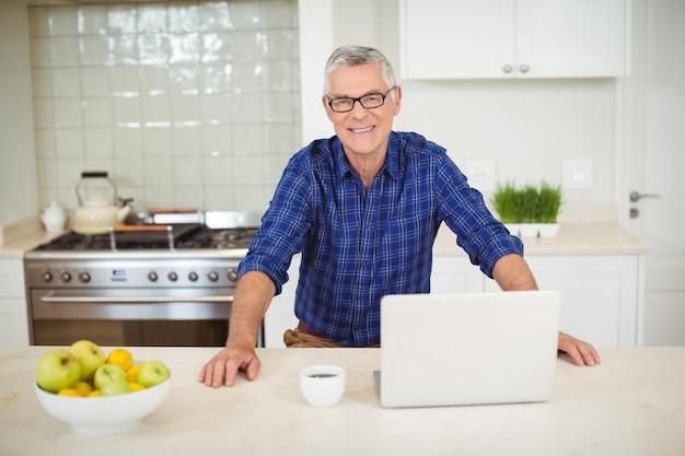 Ritratto dell'uomo senior con il computer portatile in cucina