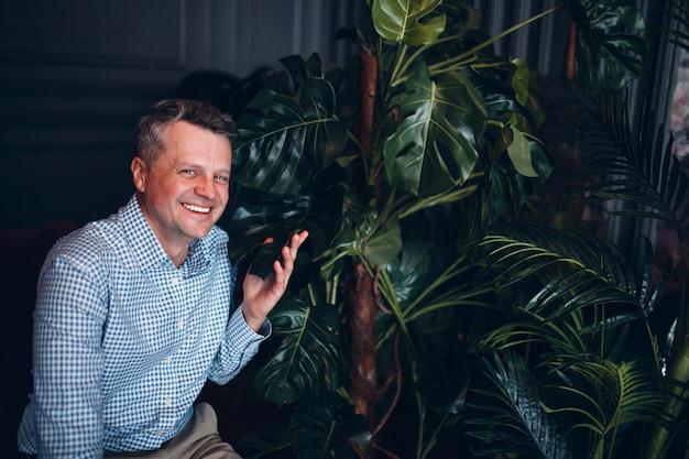Ritratto dell'uomo senior dell'adulto centrale in camicia blu con le piante verdi che guardano e sorridono. pianta da giardinaggio domestica.