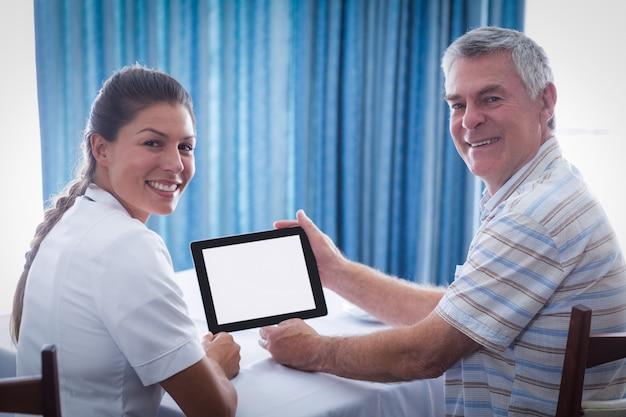 Ritratto dell'uomo senior e medico femminile che per mezzo della compressa digitale