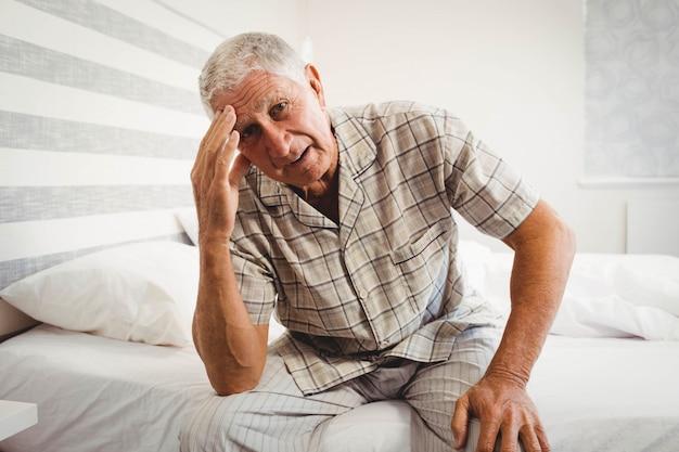 Ritratto dell'uomo senior frustrato che si siede sul letto in camera da letto